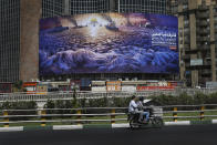 "In this Wednesday, May 29, 2019 photo, People drive at Vali-e-Asr Square in downtown Tehran where an anti-Israeli billboard is place ahead of the Al-Quds, Jerusalem, Day, Iran. Mysterious attacks on oil tankers near the strategic Strait of Hormuz show how susceptible one of the world's crucial chokepoints for global energy supplies remains, 30 years after the U.S. Navy and Iran found themselves entangled a similarly shadowy conflict. The so-called ""Tanker War"" saw American naval ships escort reflagged Kuwaiti oil tankers through the Persian Gulf and the strait after Iranian mines damaged vessels in the region. It culminated in a one-day naval battle between Washington and Tehran, as well as saw America accidentally shoot down an Iranian passenger jet, killing 290 people. (AP Photo/Ebrahim Noroozi)"