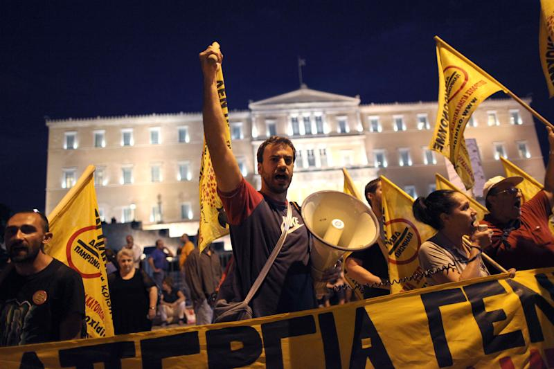 Protesters chant slogans in front of the Greek parliament during a union anti-austerity rally a day before the visit by German Chancellor Angela Merkel, in Athens on Monday, Oct. 8, 2012. Greek police have increased security and are preparing to close down large sections of the capital Athens to contain protests against Germany's Chancellor, Angela Merkel, who is visiting the city Tuesday for talks with the country's Prime Minister Antonis Samaras.(AP Photo/Petros Giannakouris)