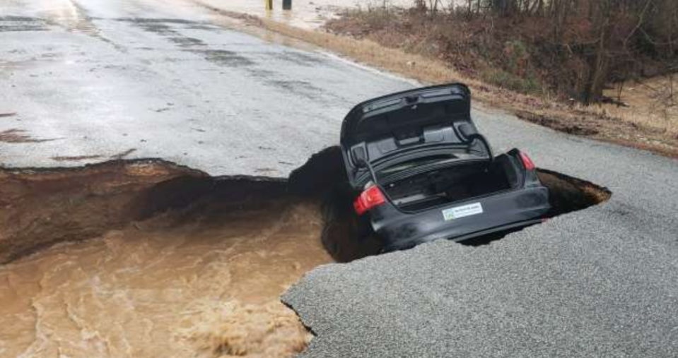 A sinkhole swallowed a car in Tennessee on Saturday, and the three passengers barely escaped. (Photo: Paul Thomas)