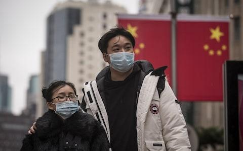 Pedestrians wearing protective masks in Shanghai, China - Credit:  Qilai Shen/Bloomberg