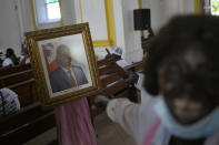 People call for justice as they point to a portrait of the late President Jovenel Moïse during a memorial service for him in the Cathedral of Cap-Haitien, Haiti, Thursday, July 22, 2021. Moïse was killed in his home on July 7. (AP Photo/Matias Delacroix)