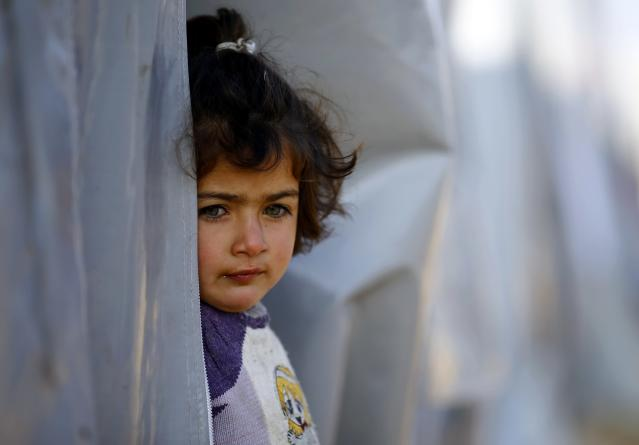 A Kurdish refugee girl from the Syrian town of Kobani peers outside her tent in a camp in the southeastern town of Suruc, Sanliurfa province October 22, 2014. REUTERS/Kai Pfaffenbach (TURKEY - Tags: MILITARY CONFLICT POLITICS)