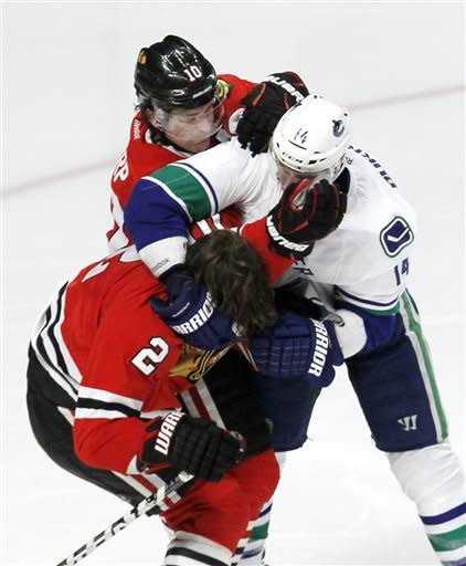 Chicago Blackhawks center Patrick Sharp (10) tries to defend teammate Duncan Keith (2) from Vancouver Canucks right wing Alex Burrows during the second period of an NHL hockey game in Chicago, Wednesday, March 21, 2012. Both Burrows and Keith received 10 minute game misconduct penalties.(AP Photo/Charles Rex Arbogast)