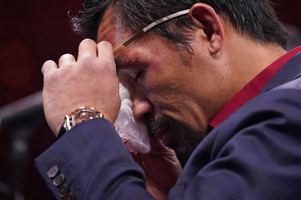 Manny Pacquiao, of the Philippines, wipes his eye at a news conference after his loss to Yordenis Ugas, of Cuba, in a welterweight championship boxing match Saturday, Aug. 21, 2021, in Las Vegas. (AP Photo/John Locher)