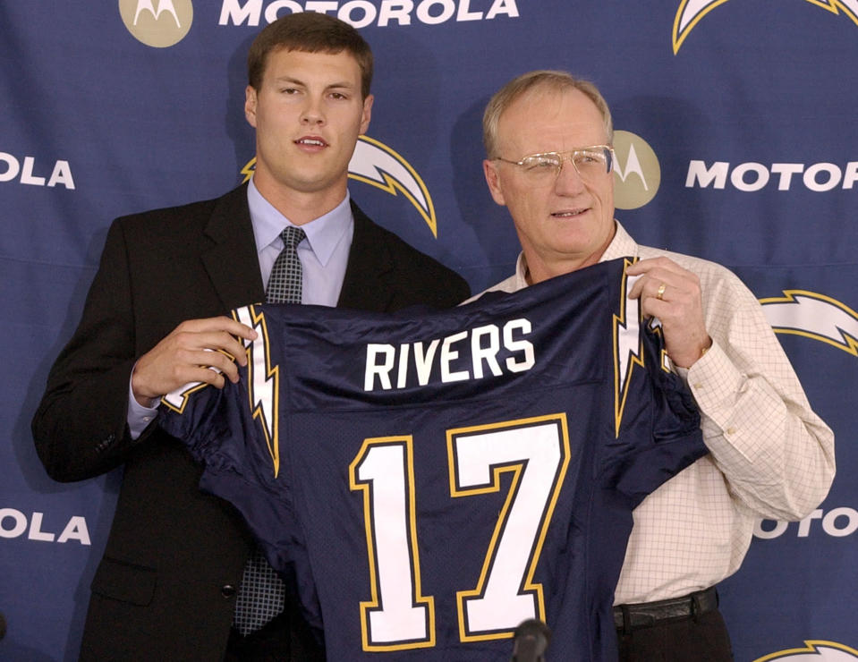 FILE - In this April 25, 2004, file photo, San Diego Chargers quarterback Philip Rivers, left, holds up his Chargers jersey with coach Marty Schottenheimer at a news conference in San Diego. The Chargers traded No. 1 draft pick Eli Manning to the New York Giants for Rivers and future draft picks. On Wednesday, Jan. 20, 2021, 39-year-old Indianapolis Colts quarterback Philip Rivers announced his retirement. (AP Photo/Denis Poroy, FIle)