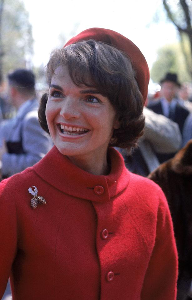 Jackie Kennedy on a trip to Canada in 1961. The First Lady matches an iconic pillbox hat to her red wool suit. Photo courtesy of Getty Images.