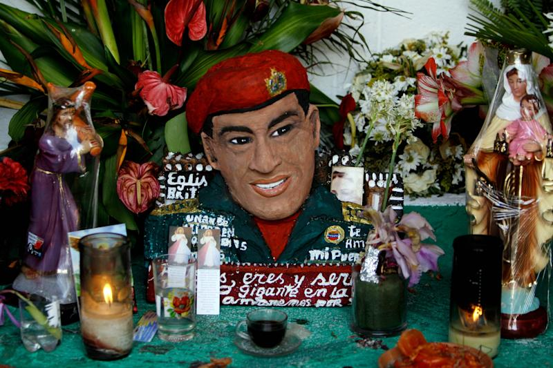"A bust of late Venezuela's President Hugo Chavez is adorned with flowers, candles and religious images inside a people's shrine built in his honor at the ""23 de Enero"" or ""23rd of January"" slum in Caracas, Venezuela, Wednesday, April 3, 2013. The shrine, named  ""Saint Hugo Chavez del 23"", has been visited by tens of thousands of Venezuelans to pay homage to a president for some, a saint for others. (AP Photo/Fernando Llano)"