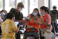 State officials assist visitors at the Daniel K. Inouye International Airport Thursday, Oct. 15, 2020, in Honolulu. A new pre-travel testing program will allow visitors who test negative for COVID-19 to come to Hawaii and avoid two weeks of mandatory quarantine goes into effect Thursday. The pandemic has caused a devastating downturn on Hawaii's tourism-based economy. Coronavirus weary residents and struggling business owners in Hawaii will be watching closely as tourists begin to return to the islands. (AP Photo/Marco Garcia)