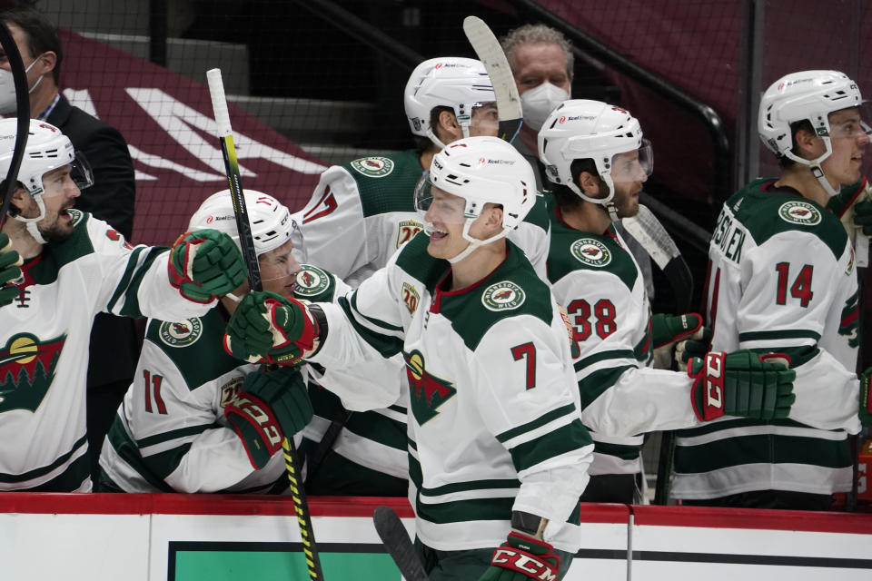 Minnesota Wild center Nico Sturm, front, is congratulated as he passes the team box after scoring a goal against the Colorado Avalanche during the third period of an NHL hockey game Wednesday, Feb. 24, 2021, in Denver. (AP Photo/David Zalubowski)