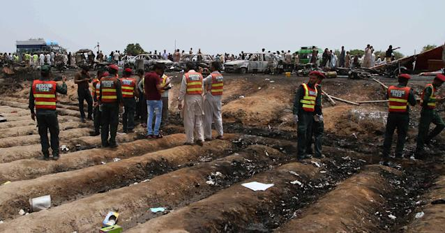 <p>Pakistani rescue workers gather at the site of an oil tanker explosion at a highway near Bahawalpur, Pakistan, Sunday, June 25, 2017. An overturned oil tanker burst into flames in Pakistan on Sunday, killing more than one hundred people who had rushed to the scene of the highway accident to gather leaking fuel, an official said. (AP Photo/Iram Asim) </p>
