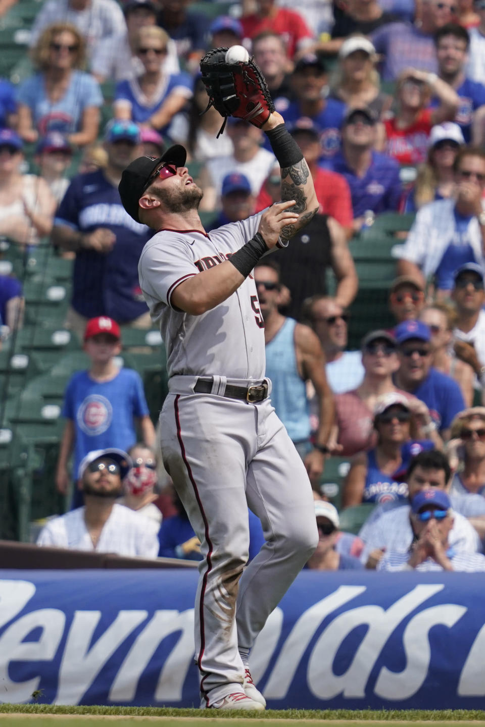 Arizona Diamondbacks first baseman Christian Walker catches a fly ball hit by Chicago Cubs' Javier Baez during the fifth inning of a baseball game in Chicago, Saturday, July 24, 2021. (AP Photo/Nam Y. Huh)