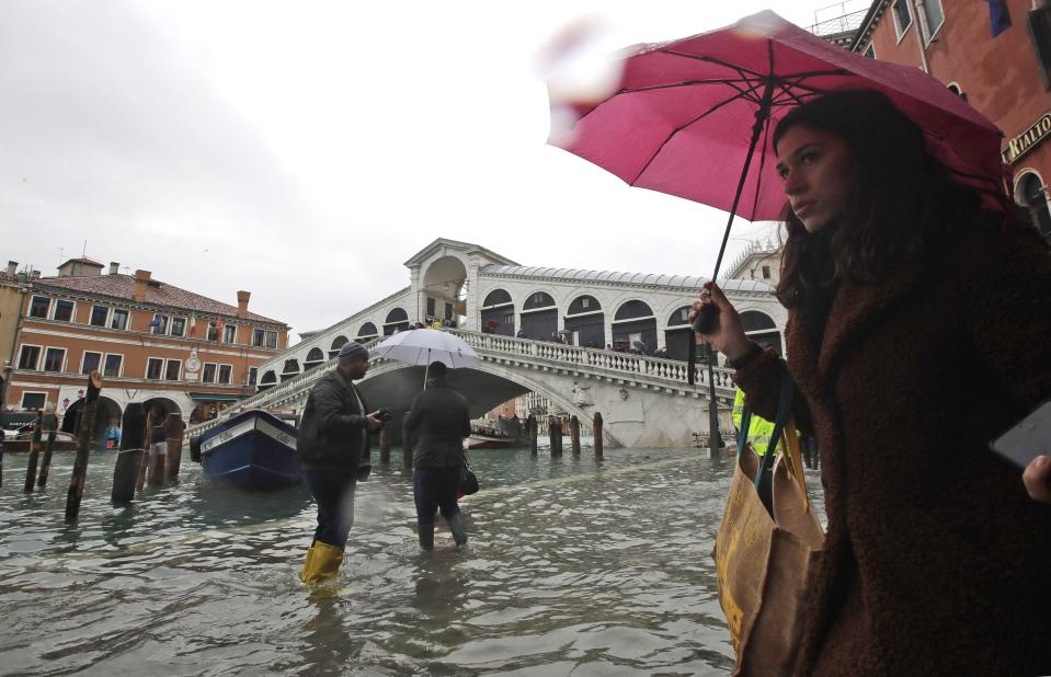 People walk near the Rialto bridge on the occasion of a high tide, in Venice, Italy, Tuesday, Nov. 12, 2019. (Photo: Luca Bruno/AP)