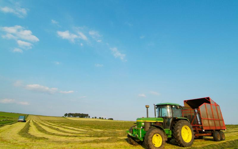 A tractor in a harvested field on a sunny day - Credit: eye35/Alamy