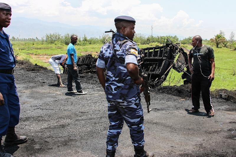 Burundi's police officers stand near the burnt truck after an attack on September 15th allegedly by a rebel from the neighboring Democratic Republic of Congo (DRC) at the border with DRC in Gatumba, western Burundi
