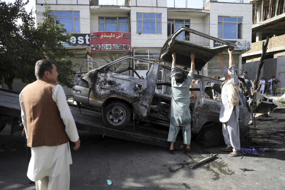 Security personnel remove a damaged minivan after a bomb explosion in Kabul, Afghanistan, Saturday, June 12, 2021. Separate bombs hit two minivans in a mostly Shiite neighborhood in the Afghan capital Saturday, killing several people and wounding others, the Interior Ministry said. (AP Photo/Rahmat Gul)