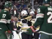 Boston Bruins' Patrice Bergeron (37) and Jake DeBrusk (74) congratulate right wing David Pastrnak (88) on a goal as the Minnesota Wild watch during the second period of an NHL hockey game Saturday, Feb. 1, 2020, in St. Paul, Minn. (AP Photo/Hannah Foslien)