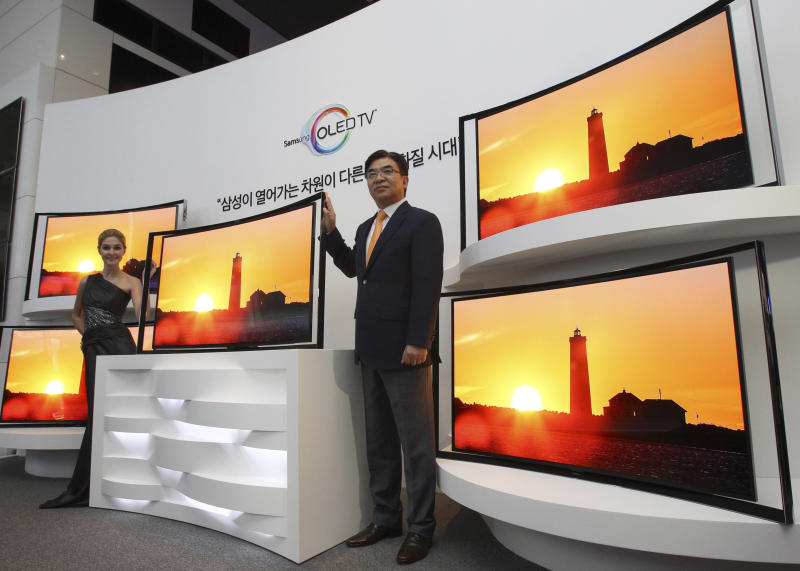 Kim Hyunsuk, the executive vice president of Samsung Electronics Co.'s TV division, right, poses with its 55-inch curved OLED TV during a press conference at its headquarters in Seoul, South Korea, Thursday, June 27, 2013. After delays, Samsung rolled out Thursday a curved TV that uses an advanced display called OLED. The 55-inch TV will sell for 15 million won ($13,000) in South Korea, more than five times the cost of LCD televisions of the same size. (AP Photo/Ahn Young-joon)