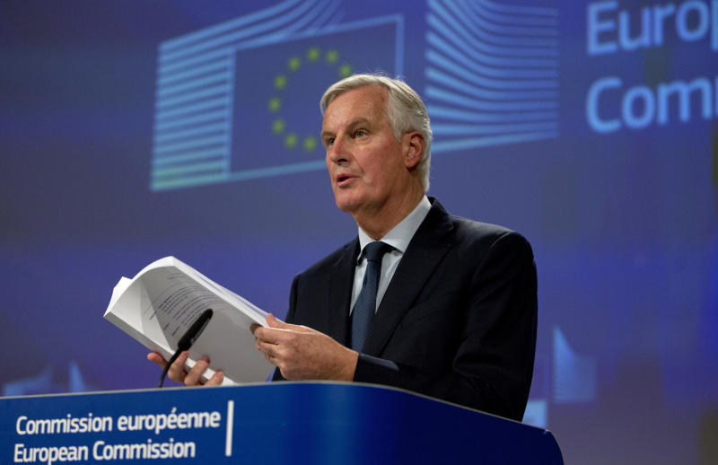 EU chief Brexit negotiator Michel Barnier leafs through the draft withdrawal agreement during a media conference in Brussels on Wednesday, Nov. 14, 2018. British Prime Minister Theresa May said that she won her Cabinet's backing for a draft divorce deal with the European Union after a marathon meeting Wednesday. (AP Photo/Virginia Mayo)