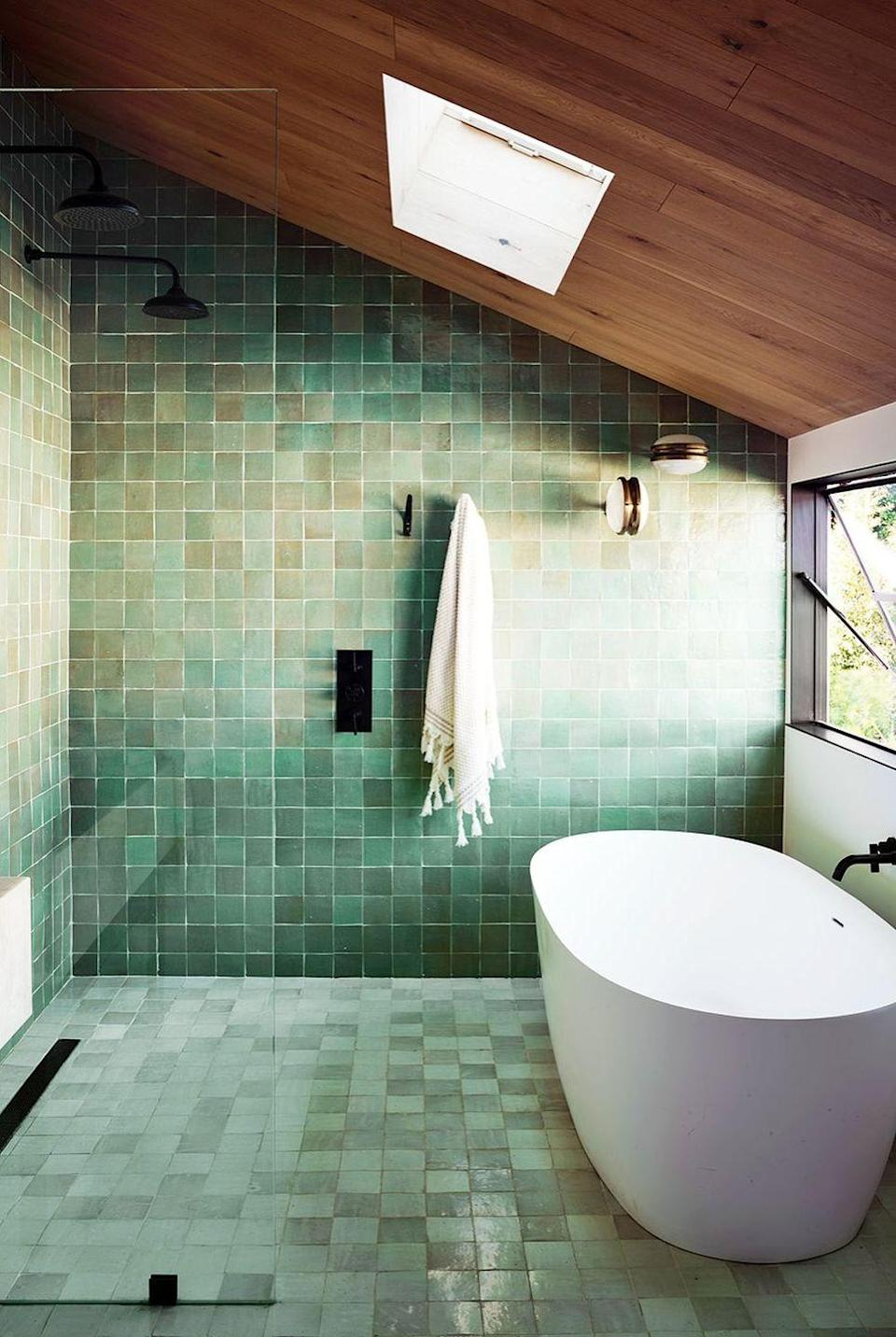 """<p>The wood panel ceiling and green zellige tiles in this bathroom by <a href=""""https://romanekdesignstudio.com/"""" rel=""""nofollow noopener"""" target=""""_blank"""" data-ylk=""""slk:Romanek Design Studio"""" class=""""link rapid-noclick-resp"""">Romanek Design Studio</a> are both ultra-modern and totally down to earth. Aside from giving the room an invigorating yet soothing surge of energy, the wall-to-wall green tile floor means that basically everything in the room will hold up well when wet. </p>"""