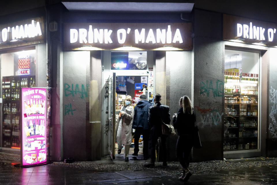 People leave and enter a so called 'Spaeti', a late night shop that sells alcohol and tobacco, amongst other things, near the RAW area, a popular nightlife spot at the district Friedrichshain in Berlin, Germany, Friday, Oct. 23, 2020. (AP Photo/Markus Schreiber)
