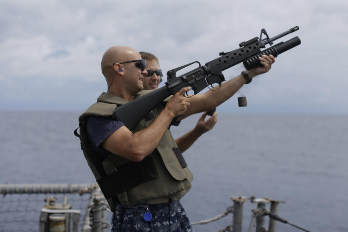 ADVANCED FOR USE SUNDAY FEB. 3 AND THEREAFTER In this Thursday, Oct. 18, 2012 photo, the captain of the USS Underwood, Peter T. Mirisola, fires a grenade launcher during small arms qualifications onboard the USS Underwood while patrolling in international waters near Panama. In the most expensive initiative in Latin America since the Cold War, the U.S. has militarized the battle against drug traffickers, spending more than $20 billion in the past decade. U.S. Army troops, Air Force pilots and Navy ships outfitted with Coast Guard counternarcotics teams are routinely deployed to chase, track and capture drug smugglers. (AP Photo/Dario Lopez-Mills)