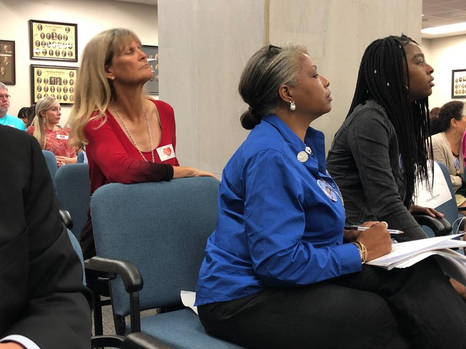 Someone for and against a bill banning abortions in South Carolina after a fetal heartbeat is detected listen to speakers at a state Senate subcommittee public hearing on Tuesday, Sept. 10, 2019, in Columbia, S.C. The bill has already passed the House and is supported by the governor. (AP Photo / Jeffrey Collins)