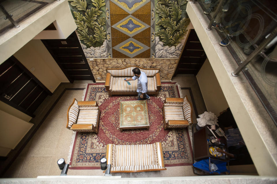 A man sanitizes the interiors of a hotel in Srinagar, Indian controlled Kashmir on Aug. 2, 2021. Tourists are returning to the valleys and mountains in Indian-controlled Kashmir, as infections in the Himalayan region and nationwide come down after a deadly second wave earlier this year. (AP Photo/Mukhtar Khan)