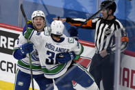 Vancouver Canucks' Nils Hoglander (36) celebrates his goal with teammate Brock Boeser (6) during the third period of an NHL game in Winnipeg, Manitoba, Monday, May 10, 2021. (Fred Greenslade/The Canadian Press via AP)