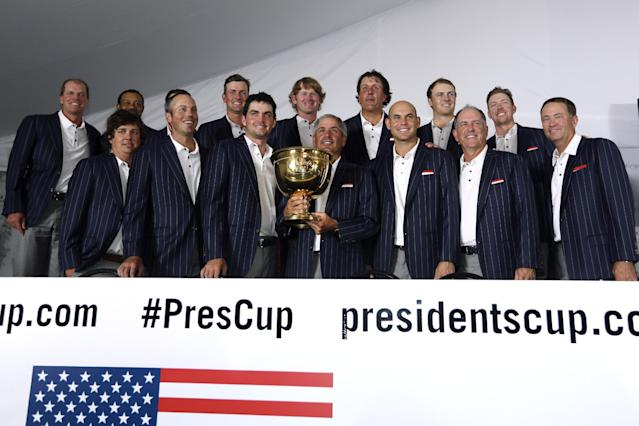 U.S. Team Captain Fred Couples lholds sthe trophy as he is joined by the United States team after winning the Presidents Cup golf tournament at Muirfield Village Golf Club Sunday, Oct. 6, 2013, in Dublin, Ohio. (AP Photo/Darron Cummings)
