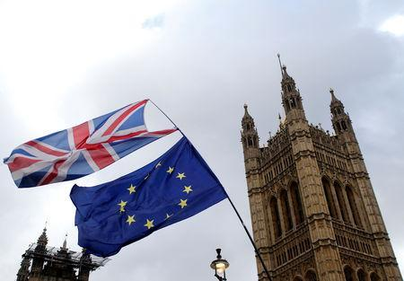 FILE PHOTO: Flags flutter outside the Houses of Parliament, ahead of a Brexit vote, in London, Britain March 13, 2019. REUTERS/Tom Jacobs