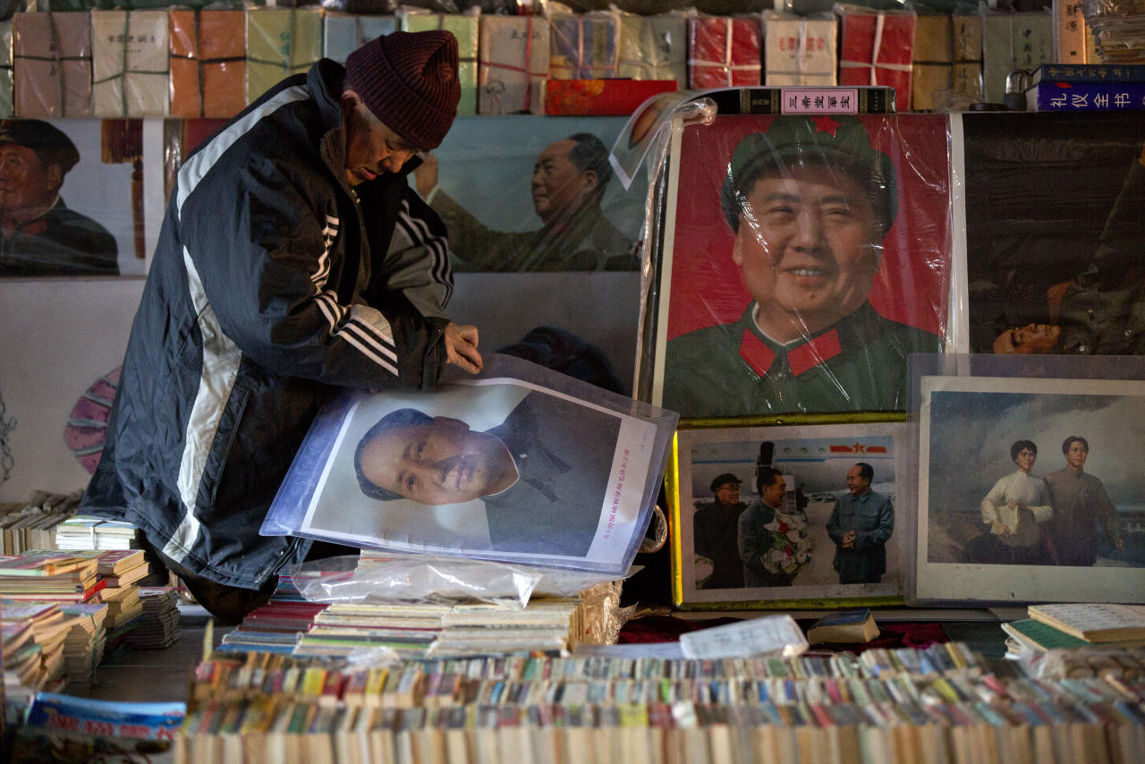 A second-hand book vendor arranges books near posters of the late Communist leader Mao Zedong at a flea market in Beijing, Thursday, Dec. 26, 2013. China's leaders bowed three times before a statue of Mao on the 120th anniversary of his birth Thursday in carefully controlled celebrations that also sought to uphold the market-style reforms that came after his death. (AP Photo/Alexander F. Yuan)