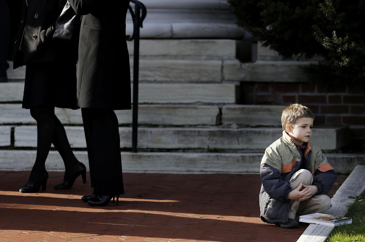 A boy sits near the steps of a church a church before the memorial service for Lauren Rousseau in Danbury, Conn., Thursday, Dec. 20, 2012. Rousseau, 30, was killed when Adam Lanza walked into Sandy Hook Elementary School in Newtown, Dec. 14, and opened fire, killing 26 people, including 20 children, before killing himself. (AP Photo/Seth Wenig)