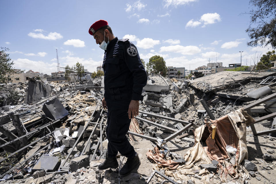 A Hamas police officer passes a crater of an airstrike that destroyed a station building prior to a cease-fire reached after an 11-day war between Gaza's Hamas rulers and Israel, in Gaza City, Saturday, May 22, 2021. (AP Photo/John Minchillo)