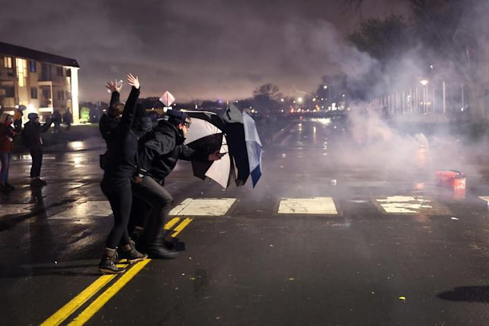 A small group of people hold open umbrellas against a cloud of smoke in a street at night.
