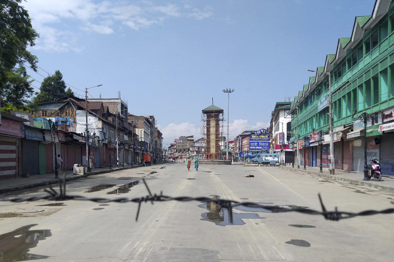 FILE- In this Thursday, Aug. 8, 2019 file photo, Kashmiri women walk at a deserted Lal Chowk square, a frequent site for anti-India protests, in Srinagar, Indian controlled Kashmir. Life is very different in the Kashmir Valley these days, under an unprecedented security crackdown to prevent an uprising after the central government unexpectedly stripped its special constitutional status, the last vestige of real autonomy for the predominantly Muslim region. (AP Photo/Sheikh Saaliq, File)
