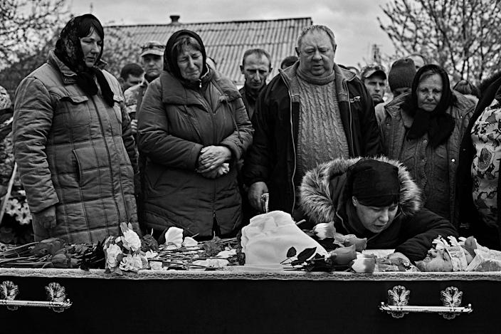<p>Private Vasily Petrovich's wife cries by the body of her husband while Vasily's relatives mourn at the graveyard of Berestivets, a tiny village 200km from Kiev in Ukraine, April 2017. (Photo: Manu Brabo/MeMo) </p>