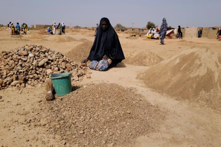 Ouedraogo Rasmata. 55, who fled from attacks of armed militants in Sahel region of Soum breaks rocks to turn into powder for sale to construction workers in an informal camp for displaced people on the outskirts of Ouagadougou
