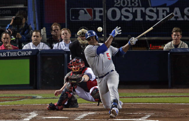 Los Angeles Dodgers' Juan Uribe (5) hits an RBI-single off Atlanta Braves starting pitcher Kris Medlen in the second inning during Game 1 of the National League Divisional Series, Thursday, Oct. 3, 2013, in Atlanta. (AP Photo/Dave Martin)