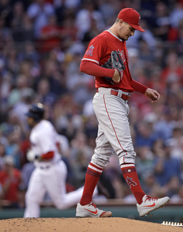 Los Angeles Angels starting pitcher Andrew Heaney walks off the mound as Boston Red Sox's J.D. Martinez rounds the bases on a three-run home run during the second inning of a baseball game at Fenway Park in Boston, Wednesday, June 27, 2018. (AP Photo/Charles Krupa)