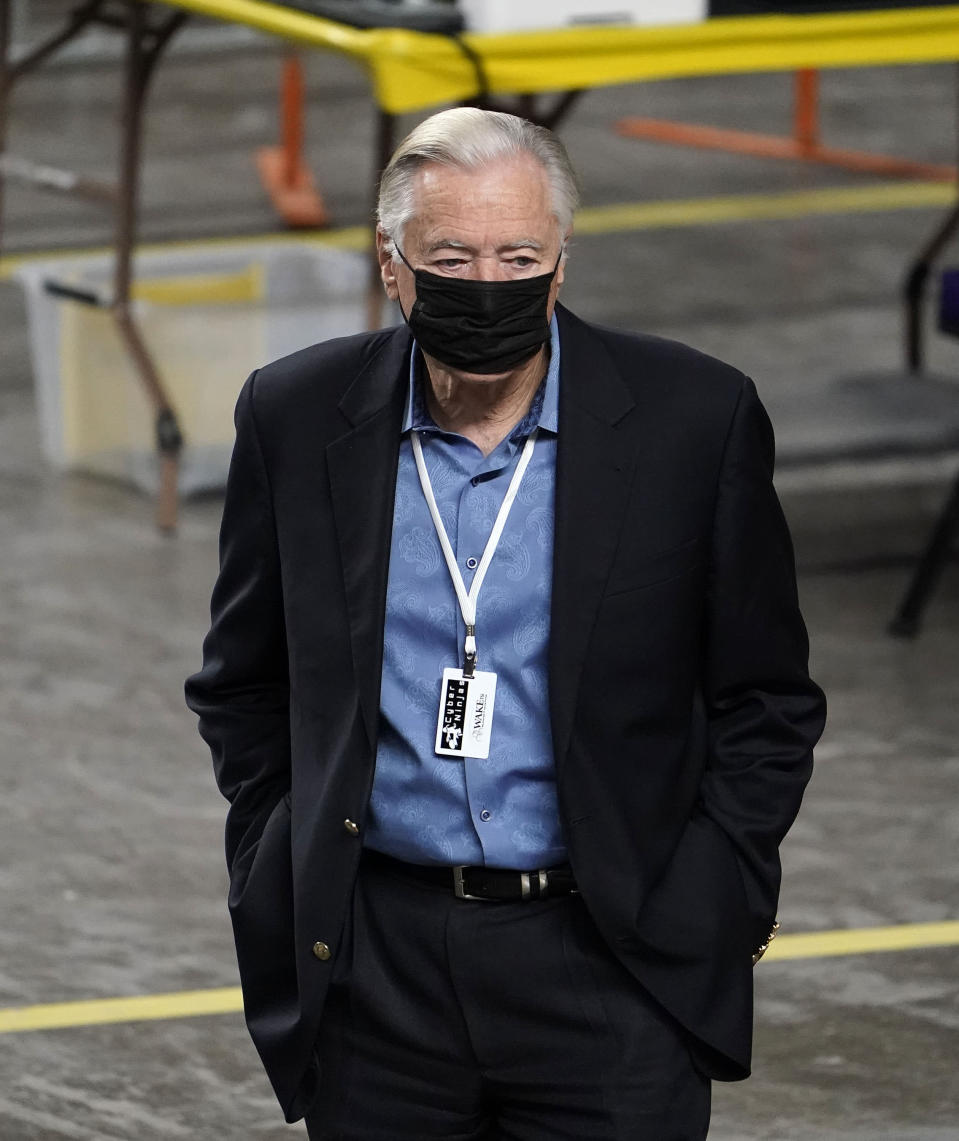 A man wearing a Cyber Ninjas badge watches from the floor as the Maricopa County ballots cast in the 2020 general election are being examined and recounted by contractors working for Florida-based company, Cyber Ninjas, who was hired by the Arizona State Senate at Veterans Memorial Coliseum in Phoenix, Thursday, April 29, 2021. (Rob Schumacher/The Arizona Republic via AP, Pool)