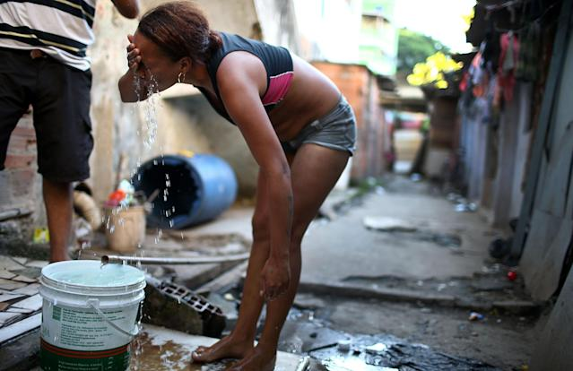 RIO DE JANEIRO, BRAZIL - MARCH 18: Resident Janubie washes her face with fresh water from an open pipe near her house in an impoverished area in the unpacified Complexo da Mare slum complex, one of the largest 'favela' complexes in Rio, on March 18, 2014 in Rio de Janeiro, Brazil. The group of 16 communities house around 130,000 residents while plagued by violence and poverty and dominated by drug gangs. Mare is located close to Rio's international airport and has been mentioned as a likely pacification target for the police. Rio's Police Pacification Unit (UPP) now controls 38 of the city favelas amid the city's efforts to improve security ahead of the 2014 FIFA World Cup and 2016 Olympic Games. (Photo by Mario Tama/Getty Images)