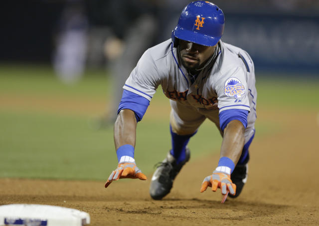 New York Mets' Eric Young Jr. dives back to first while playing the San Diego Padres during the seventh inning in a baseball game on Saturday, Aug. 17, 2013, in San Diego. Young Jr went on to steal second and third base in the inning. (AP Photo/Gregory Bull)