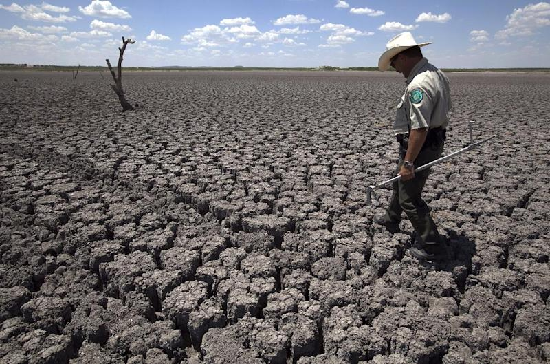 FILE - In this Wednesday, Aug. 3, 2011 file photo, Texas State Park police officer Thomas Bigham walks across the cracked lake bed of O.C. Fisher Lake in San Angelo, Texas. A combination of the long periods of 100-plus degree days and the lack of rain in the drought-stricken region has dried up the lake that once spanned over 5400 acres. The year 2011 brought a record heat wave to Texas, massive floods in Bangkok and an unusually warm November in England. How much has global warming boosted the chances of events like that? Quite a lot in Texas and England, but apparently not at all in Bangkok, according to new analyses released Tuesday, July 10, 2012. Researchers calculated that global warming has made such a Texas heat wave about 20 times more likely to happen during a La Nina year. (AP Photo/Tony Gutierrez)