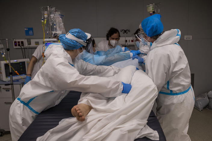 A medical team of the new Nurse Isabel Zendal Hospital rotates a patient at the COVID-19 ICU ward in Madrid, Spain, Monday, Jan. 18, 2021. As the coronavirus curve of contagion turned increasingly vertical after Christmas and New Year's, the Zendal has been busy. On Monday, 392 virus patients were being treated, more than in any other hospital in the Madrid region. (AP Photo/Bernat Armangue)