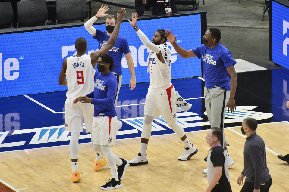 Los Angeles Clippers center Serge Ibaka (9) high-fives teammates after scoring a basket at the end of the first half of the team's NBA basketball game against the Memphis Grizzlies on Friday, Feb. 26, 2021, in Memphis, Tenn. (AP Photo/Brandon Dill)