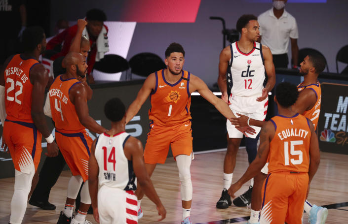 Phoenix Suns guard Devin Booker (1) celebrates with teammates in the first half of an NBA basketball game against the Washington Wizards in Lake Buena Vista, Fla., Friday, July 31, 2020. (Kim Klement/Pool Photo via AP)