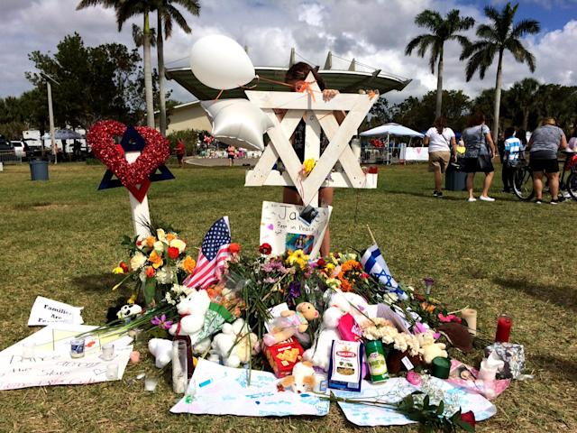 <p>A girl writes a note at a makeshift memorial for Marjory Stoneman Douglas High School shooting victim, Jaime Guttenberg, at Pine Trail Park, Parkland, Fla., Feb. 19, 2018. (Photo: Mindy Katzman/Yahoo News) </p>