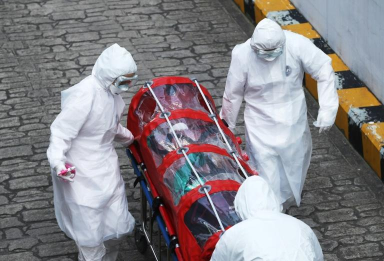 Medics wearing protective gear carry a patient infected with the COVID-19 virus to hospital in Seoul