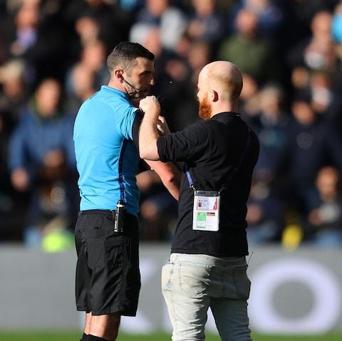 Referee Michael Oliver receives some technical support during the Premier League match between Watford FC and Tottenham Hotspur - Credit: GETTY IMAGES