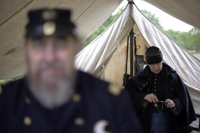 In this Friday, May 24, 2013 photo, Richard Baldino, right, accompanied by Dave Morris, both portraying army surgeons with the 2nd Division 11th Corps Army of Potomac, cleans out his pipe at the George Spangler Farm that served as a field hospital during the Civil War, in Gettysburg, Pa. Tens of thousands of visitors are expected for the 10-day schedule of events that begin June 29 to mark 150th anniversary of the Battle of Gettysburg that took that took place July 1-3, 1863. (AP Photo/Matt Rourke)
